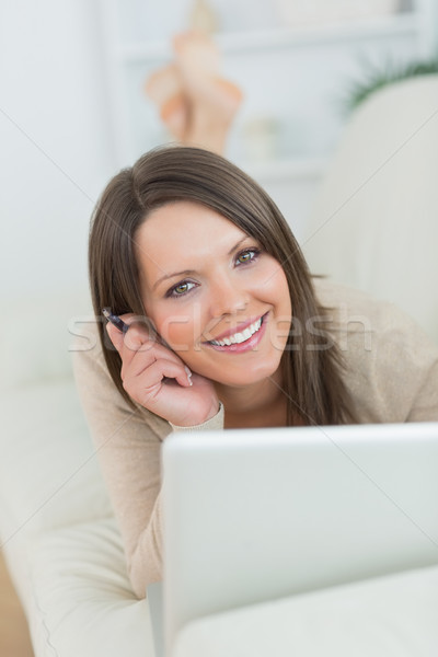smiling woman using her laptop lying on the sofa in the living room Stock photo © wavebreak_media