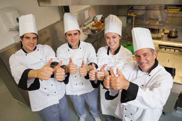 Team of Chef's giving thumbs up in restaurant kitchen Stock photo © wavebreak_media