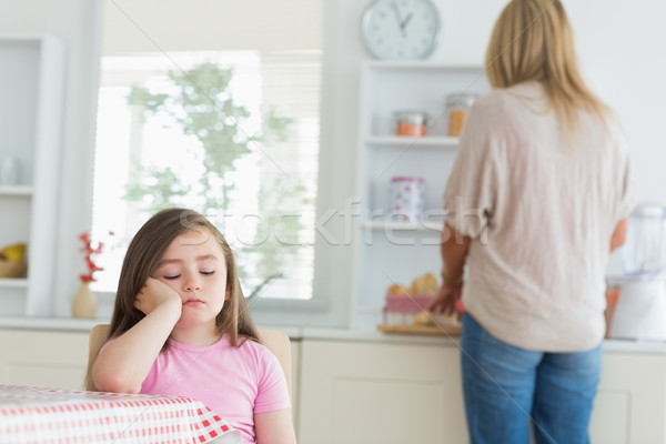 Child falling asleep at kitchen table with mother working on counter Stock photo © wavebreak_media