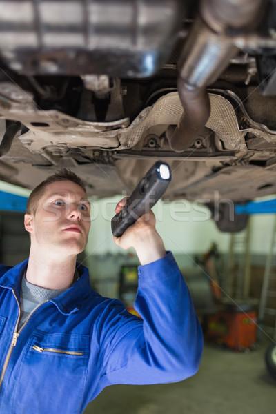 Repairman with flashlight examining under car Stock photo © wavebreak_media