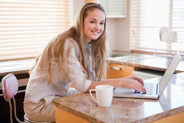 肖像 笑顔の女性 ラップトップを使用して 笑みを浮かべて 若い女性 キッチン ストックフォト © wavebreak_media