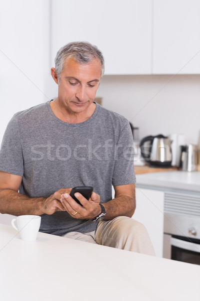 Mature man touching his smartphone Stock photo © wavebreak_media