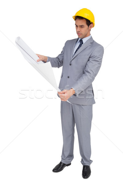 Serious architect with hard hat looking at plans Stock photo © wavebreak_media