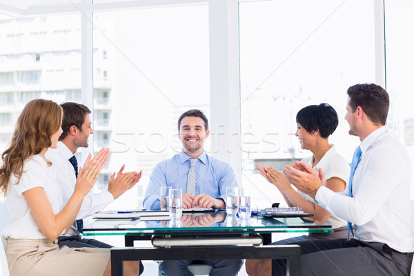 Executives clapping around conference table Stock photo © wavebreak_media