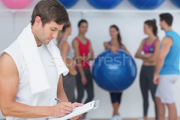 Trainer writing in clipboard with fitness class in background Stock photo © wavebreak_media