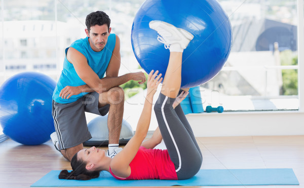 Trainer helping woman with her exercises at gym Stock photo © wavebreak_media