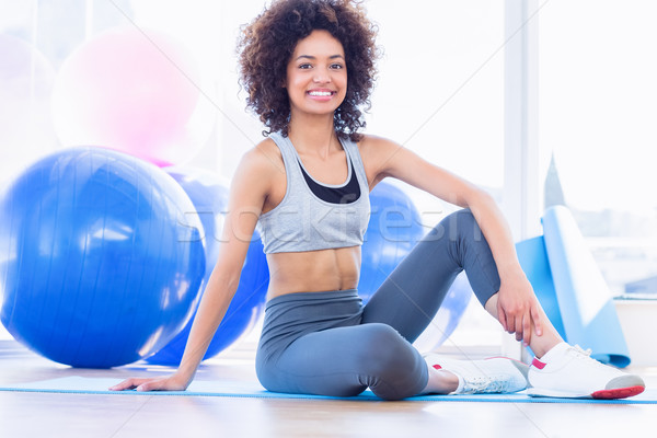 Stock photo: Full length of a fit woman on exercise mat in fitness studio