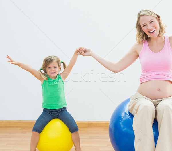 Happy pregnant woman bouncing on exercise ball with young daught Stock photo © wavebreak_media