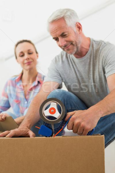 Happy couple sealing cardboard moving boxes Stock photo © wavebreak_media