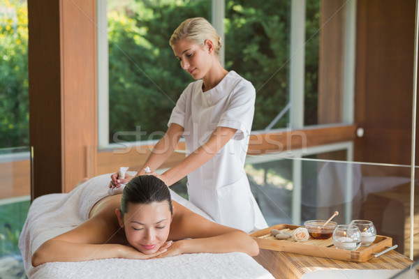 Content brunette enjoying a herbal compress massage Stock photo © wavebreak_media