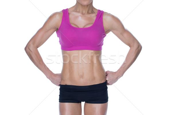 Female bodybuilder posing in pink sports bra and shorts mid sect Stock photo © wavebreak_media