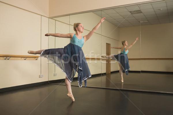 Stock photo: Beautiful ballerina dancing in front of mirror
