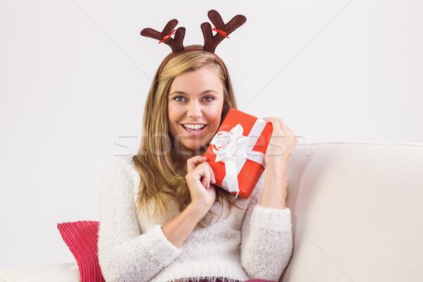 Festive blonde relaxing on sofa with gift Stock photo © wavebreak_media