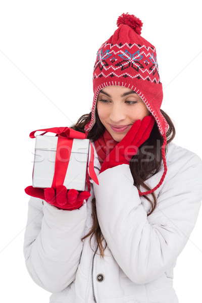 Content brunette in winter clothes holding gift Stock photo © wavebreak_media