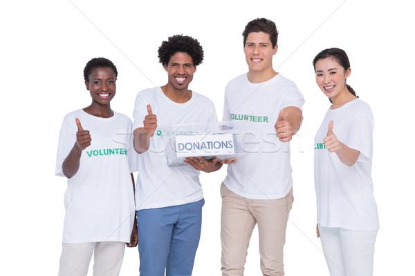 Young smiling volunteers collecting donations Stock photo © wavebreak_media