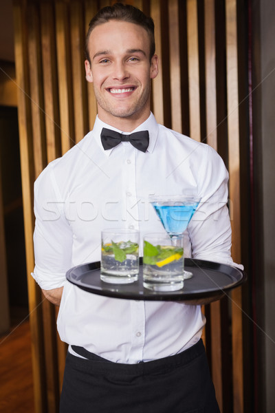 Cheerful young waiter holding tray with cocktails Stock photo © wavebreak_media