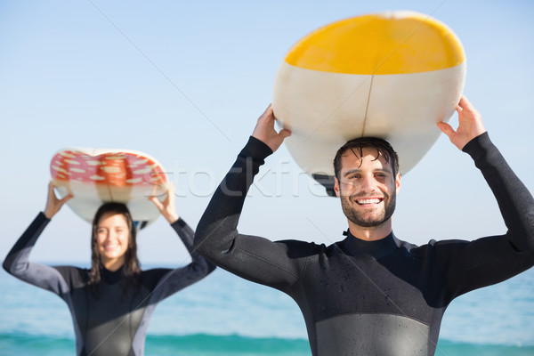 happy couple in wetsuits with surfboard on a sunny day Stock photo © wavebreak_media