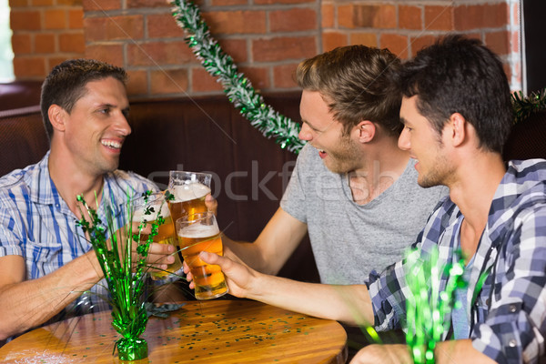 Happy friends toasting with pints of beer on patricks day Stock photo © wavebreak_media