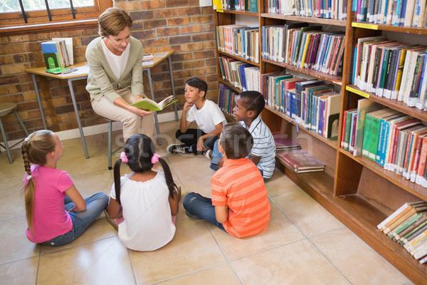 Cute pupils and teacher having class in library  Stock photo © wavebreak_media