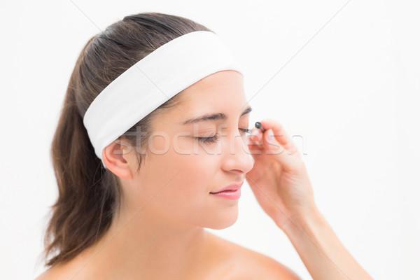 Hand applying mascara to beautiful woman Stock photo © wavebreak_media