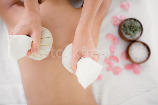 Pretty woman enjoying a herbal compress massage Stock photo © wavebreak_media