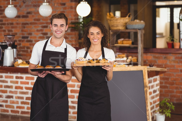 Smiling waiter and waitress holding tray with muffins Stock photo © wavebreak_media