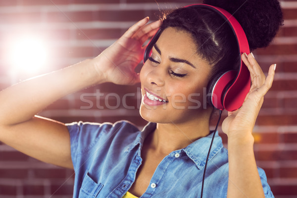 A smiling woman being transported by music Stock photo © wavebreak_media