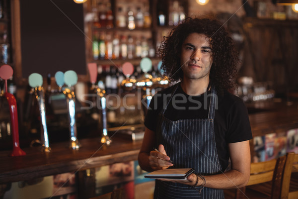 Portrait of young waiter writing on diary Stock photo © wavebreak_media