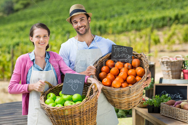 Portrait of smiling couple holding fresh fruits in wicker baskets Stock photo © wavebreak_media