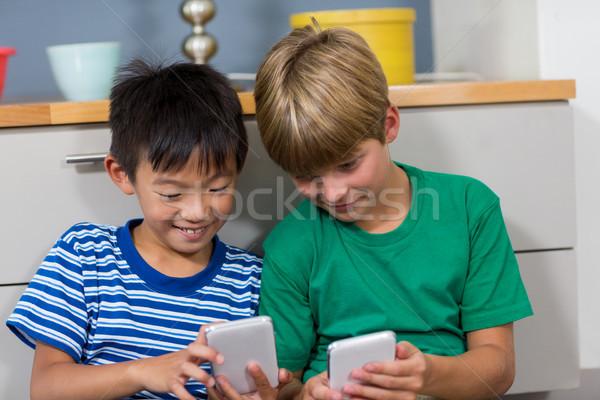Happy siblings using mobile phone in living room Stock photo © wavebreak_media