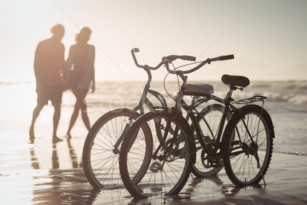Bicycles parking on shore with couple in background Stock photo © wavebreak_media