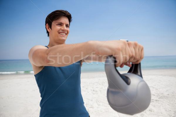 Smiling young man holding kettlebell at beach Stock photo © wavebreak_media