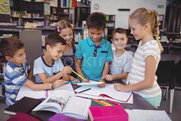 Attentive schoolkid using digital tablet in library Stock photo © wavebreak_media