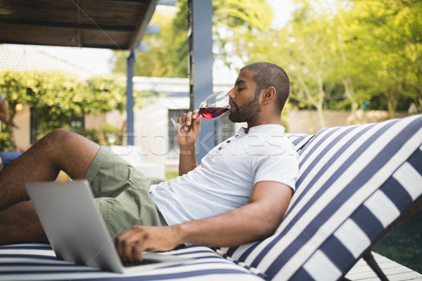 Man drinking red wine while relaxing at porch Stock photo © wavebreak_media