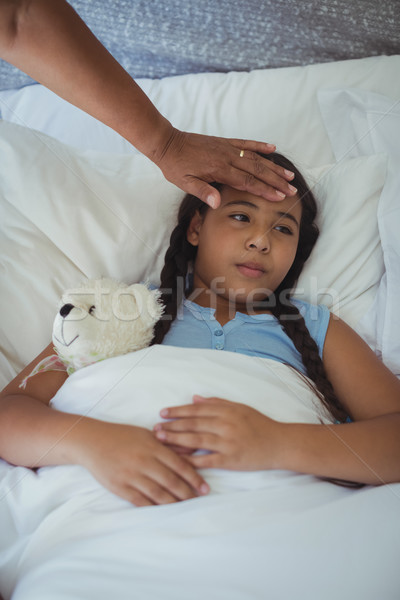 Grandmother comforting sick granddaughter in bed room Stock photo © wavebreak_media
