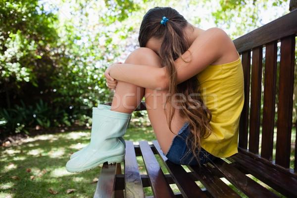 Side view of upset girl sitting on wooden bench Stock photo © wavebreak_media