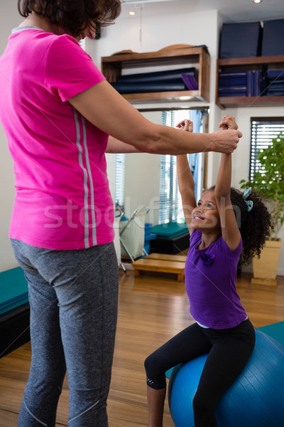 Female physiotherapist helping girl patient in performing exercise with dumbbell Stock photo © wavebreak_media