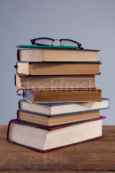 Spectacles and pencil on book stack at desk Stock photo © wavebreak_media
