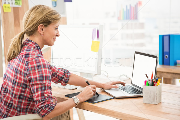 Casual designer working with digitizer and laptop Stock photo © wavebreak_media