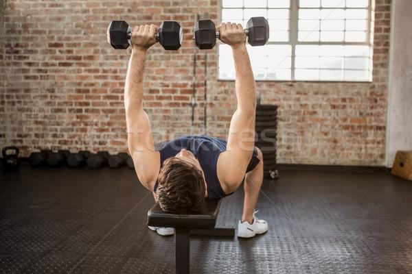 Man lifting dumbbells while lying on exercise bench Stock photo © wavebreak_media
