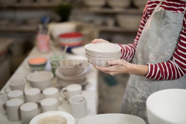 Mid section of female potter holding stack of bowls Stock photo © wavebreak_media