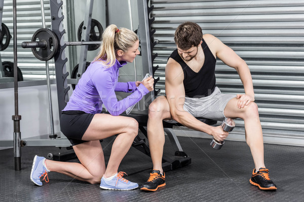 Female trainer assisting man with dumbbells Stock photo © wavebreak_media