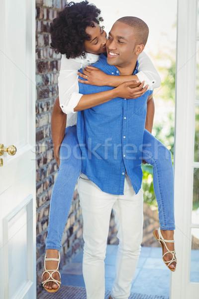 Handsome man giving piggy back to his girlfriend Stock photo © wavebreak_media
