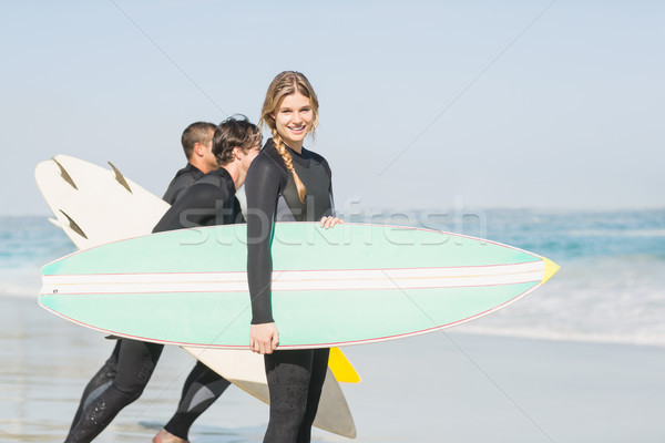 Portrait of surfer woman with surfboard standing on the beach Stock photo © wavebreak_media