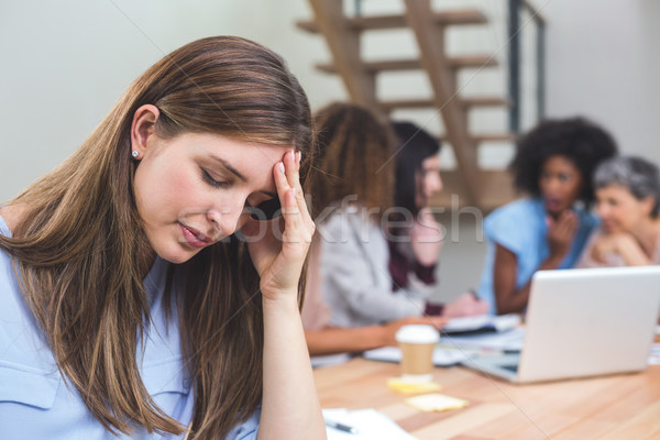 Tenso mujer de negocios sesión oficina mano frente Foto stock © wavebreak_media