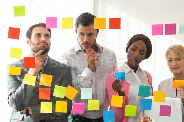 Ludzi biznesu patrząc przyczepny zauważa szkła ściany Zdjęcia stock © wavebreak_media