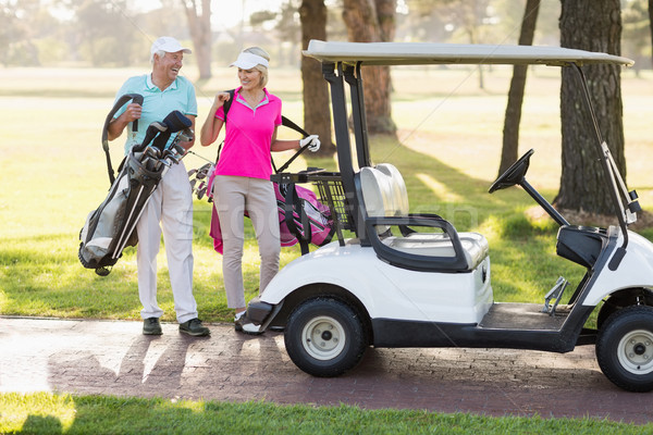 Happy mature golfer couple by golf buggy Stock photo © wavebreak_media