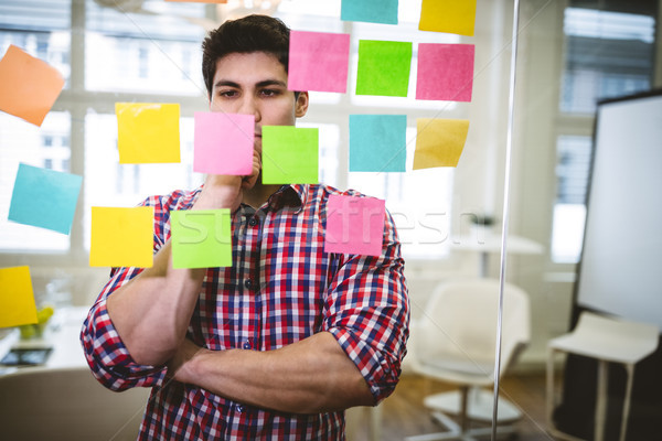 Thoughtful businessman looking at sticky notes on glass Stock photo © wavebreak_media
