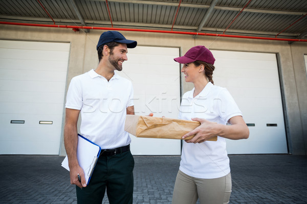 Happy delivery man and woman standing with clipboard and parcel Stock photo © wavebreak_media