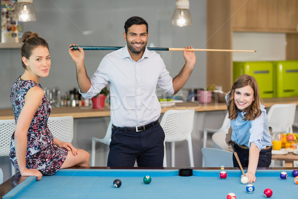 Smiling business colleagues playing pool in office space Stock photo © wavebreak_media